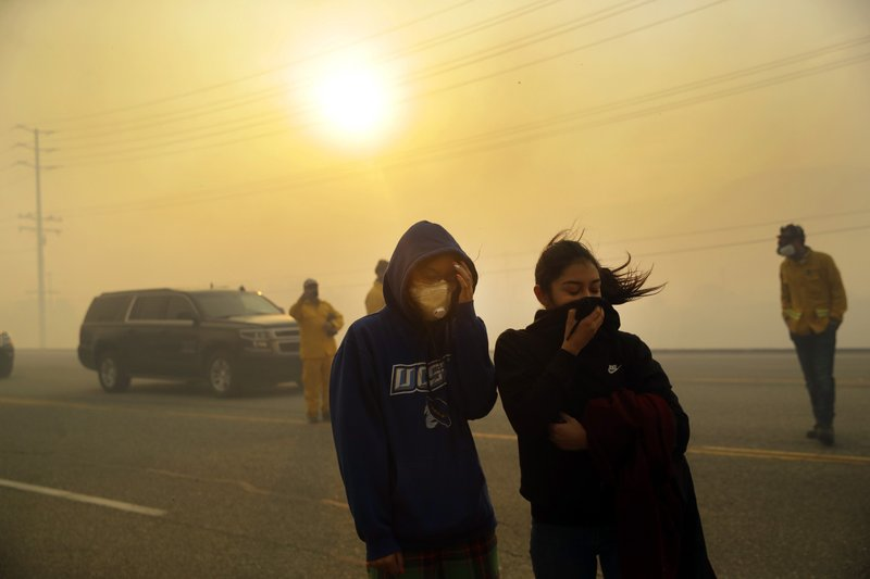 Natalie Acosta, left, and Lea Rivera cover their faces from the smoke created by the Easy Fire Wednesday, Oct. 30, 2019, in Simi Valley, Calif. Driven by powerful Santa Ana winds, the brush fire broke out before dawn between the cities of Simi Valley and Moorpark north of Los Angeles and exploded to more than 1,300 acres (526 hectares), threatening 6,500 homes, Ventura County officials said. (AP Photo/Marcio Jose Sanchez)