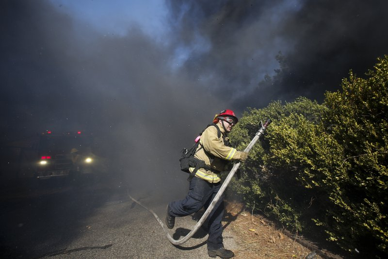 A firefighter battles a wildfire near a ranch in Simi Valley, Calif., Wednesday, Oct. 30, 2019. (AP Photo/Ringo H.W. Chiu)