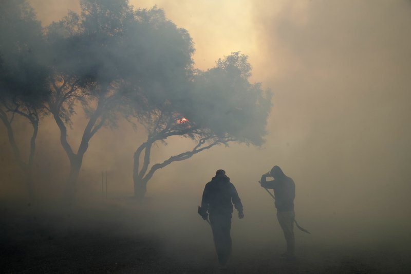Dean Cato, left, and his son Robert use shovels to try to put out hotspots caused by the Easy fire at American Soil and Nursery Wednesday, Oct. 30, 2019, in Simi Valley, Calif.  A new wildfire erupted Wednesday in wind-whipped Southern California, forcing the evacuation of the Ronald Reagan Presidential Library and nearby homes, as both ends of the state struggled with blazes, dangerously gusty weather and deliberate blackouts. (AP Photo/Marcio Jose Sanchez)