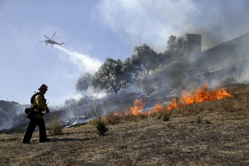 Trinh Nguyen, of the Camarillo Fire Dept, monitors the advance of the Easy Fire as a helicopter makes a water drop Wednesday, Oct. 30, 2019, in Simi Valley, Calif. Driven by powerful Santa Ana winds, the brush fire broke out before dawn between the cities of Simi Valley and Moorpark north of Los Angeles and exploded to more than 1,300 acres (526 hectares), threatening 6,500 homes, Ventura County officials said.  (AP Photo/Marcio Jose Sanchez)
