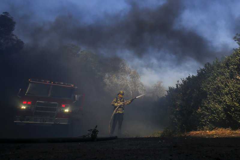 Firefighter Brett Reed battles a wildfire near a ranch in Simi Valley, Calif., Wednesday, Oct. 30, 2019. (AP Photo/Ringo H.W. Chiu)