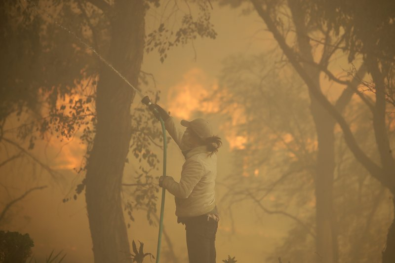 Beth Rivera hoses down her property as the Easy fire approaches Wednesday, Oct. 30, 2019, in Simi Valley, Calif.  Driven by powerful Santa Ana winds, the brush fire broke out before dawn between the cities of Simi Valley and Moorpark north of Los Angeles and exploded to more than 1,300 acres (526 hectares), threatening 6,500 homes, Ventura County officials said. (AP Photo/Marcio Jose Sanchez)