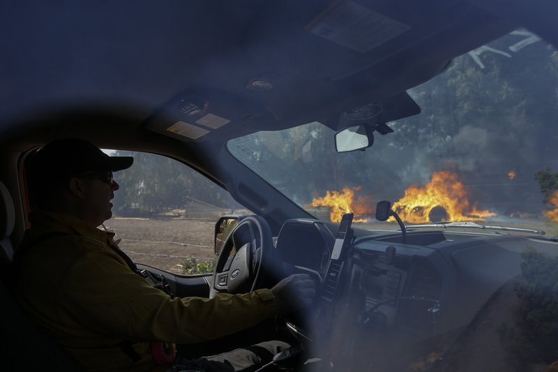Firefighter Kris McDonald keeps watch on the wildfire burning near a ranch in Simi Valley, Calif., Wednesday, Oct. 30, 2019. (AP Photo/Ringo H.W. Chiu)