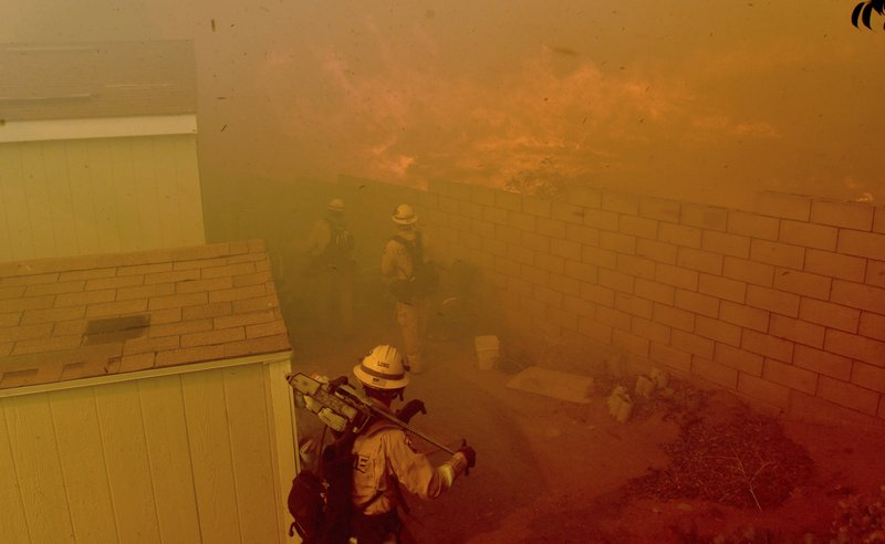 Flames approach the backyards of mobile homes in Santiago Estates at Pedley during the Hill Fire in Jurupa Valley, Calif., Wednesday Oct 30, 2019. (Will Lester/The Orange County Register via AP)