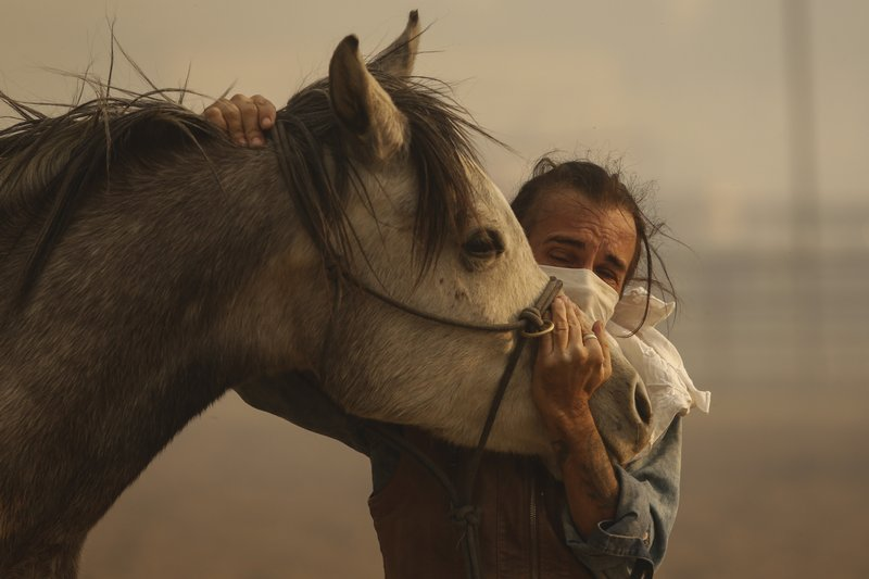 Fabio Losurdo comforts his horse, Smarty, at a ranch in Simi Valley, Calif., Wednesday, Oct. 30, 2019. A brush fire broke out just before dawn in the Simi Valley area north of Los Angeles. (AP Photo/Ringo H.W. Chiu)