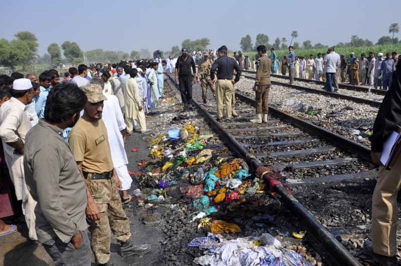 Pakistani soldiers and officials examine a train damaged by a fire in Liaquatpur, Pakistan, Thursday, Oct. 31, 2019. A massive fire engulfed three carriages of the train traveling in the country's eastern Punjab province (AP Photo/Siddique Baluch)