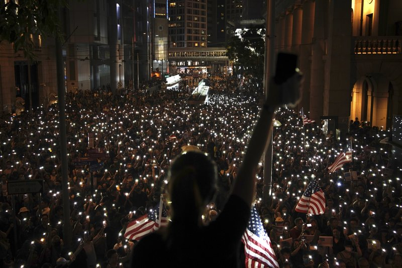 Demonstrators in Hong Kong ask the U.S. for help by flying its flag and lighting flashlights during a peaceful demonstration in Hong Kong's downtown business district on Oct. 14, 2019 (AP Photo/Felipe Dana)