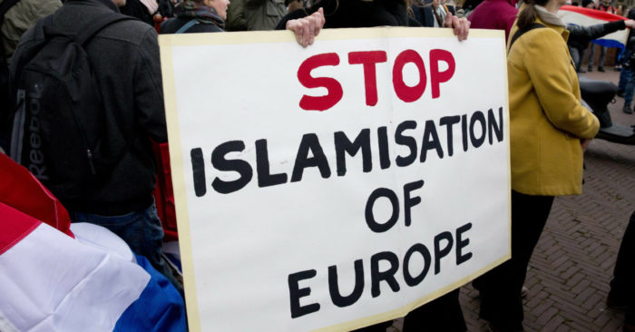 "A French citizen holds a poster that reads: ""Stop Islamisation of Europe"". (AP/Peter Dejong File)"