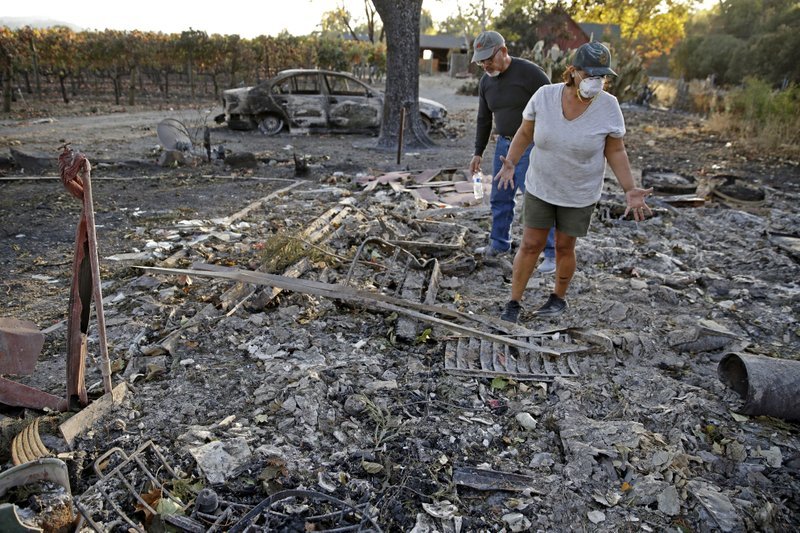 Justo and Bernadette Laos look through the charred remains of the home they rented that was destroyed by the Kincade Fire near Geyserville, Calif., Thursday, Oct. 31, 2019. (AP Photo/Charlie Riedel)