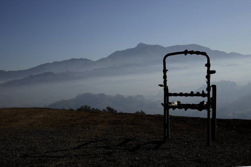 A charred lawn chair overlooks a valley filled with smoke from the Kincade Fire near Healdsburg, Calif., Nov. 1, 2019. (AP Photo/Charlie Riedel)