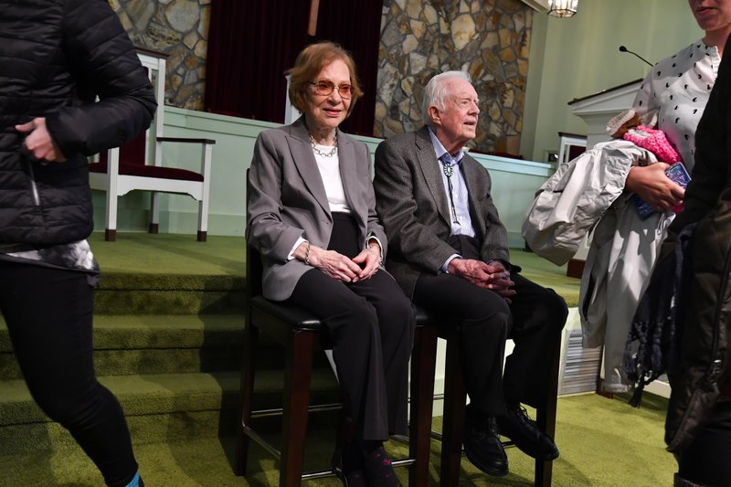 Former U.S. President Jimmy Carter and former first lady Rosalynn Carter, left, sit as guests of Maranatha Baptist Church come and go to have their photo made with them, after Jimmy taught Sunday school there, Sunday, Nov. 3, 2019, in Plains, Ga. (AP Photo/John Amis)