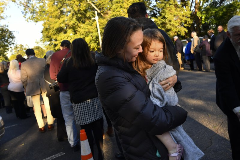 Sarah Dyer holds two year old daughter Imogen, as they stand in line to attend Sunday school taught by Former President Jimmy Carter at Maranatha Baptist Church, Sunday, Nov. 3, 2019, in Plains, Ga. The Dyer family of six drove straight from Chicago listening to audio books by Carter along the way. (AP Photo/John Amis)