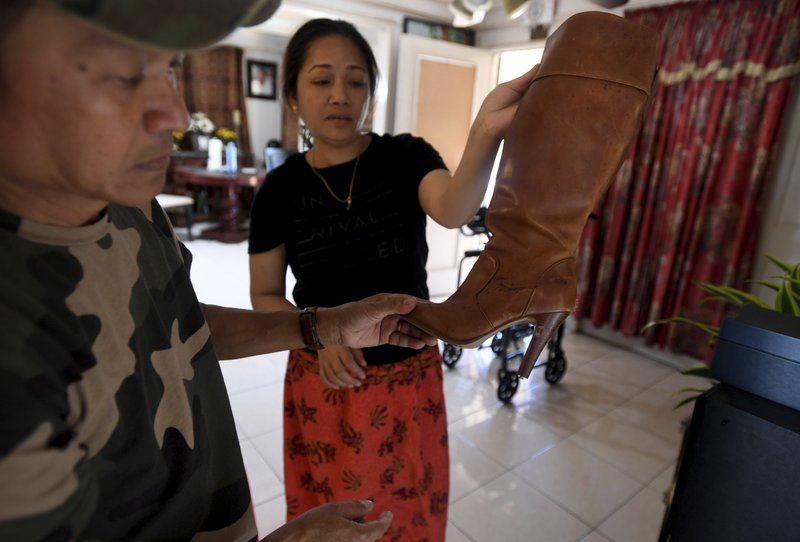 Chanchenda Hou, and Da Heng, hold up a victims' boot with bullet holes in it after the Halloween themed birthday party hosted at their home ended with 3 dead and 9 injured.  (Brittany Murray/The Orange County Register via AP)