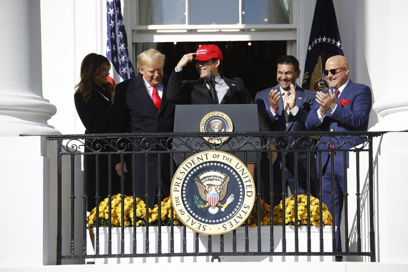 President Donald Trump stands with Washington Nationals catcher Kurt Suzuki, during an event to honor the 2019 World Series champion Washington Nationals on the balcony of the White House, Monday, Nov. 4, 2019, in Washington, as First Lady Melania Trump, left, and Washington Nationals coach Dave Martinez, second from right and general manager Mike Rizzo, far right, look on. Suzuki is pointing to a Make America Great Again hat. (AP Photo/Patrick Semansky)