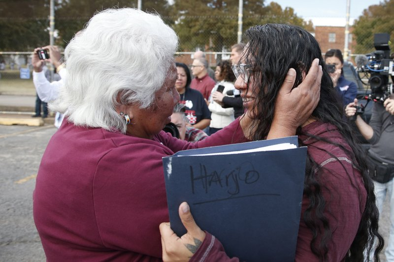 Sally Taylor, left, embraces her granddaughter Tess Harjo, right, after Harjo was released from the Eddie Warrior Correctional Center Monday, Nov. 4, 2019 in Taft, Okla. More than 450 inmates walked out the doors of prisons across Oklahoma on Monday as part of what state officials say is the largest single-day mass commutation in U.S. history. (AP Photo/Sue Ogrocki)