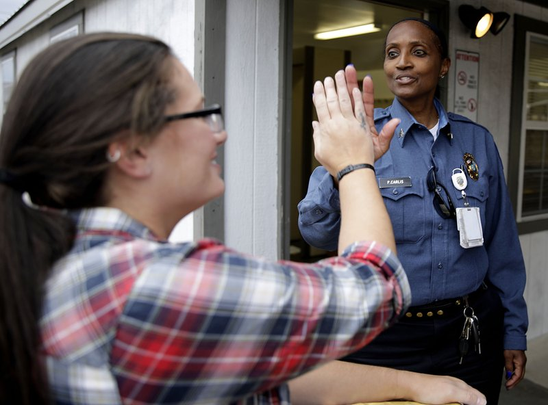 Danni Roberts is given a high five from Correctional officer Sgt. Pamela Carlis as she leaves Dr. Eddie Warrior Correctional Center after hundreds of inmates had their sentences commuted by the state Monday, Nov. 4, 2019.  (Mike Simons/Tulsa World via AP)