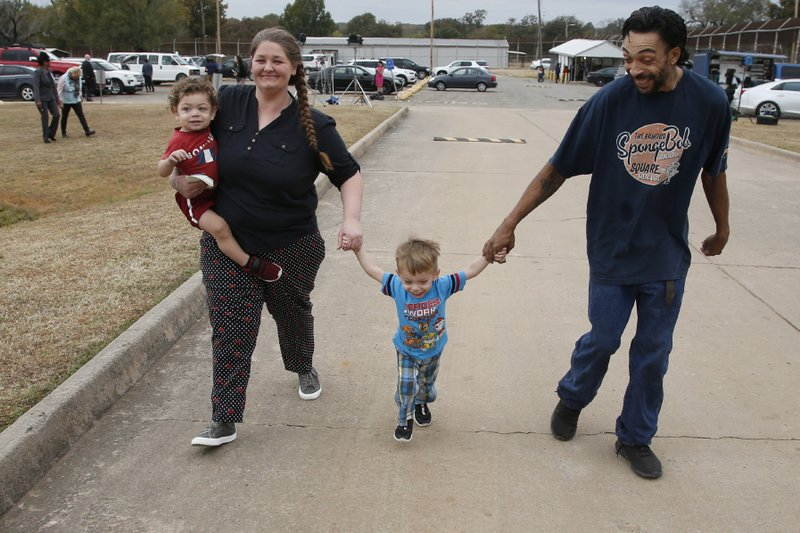 Recently released inmate Donnie Crow, left, holds her 17-month-old son Fayedon Davis as she walks from the Eddie Warrior Correctional Center with Christopher Davis Sr. and son 32-month old Christopher Davis II, following her release Monday, Nov. 4, 2019 in Taft, Okla. More than 450 inmates walked out the doors of prisons across Oklahoma on Monday as part of what state officials say is the largest single-day mass commutation in U.S. history. (AP Photo/Sue Ogrocki)