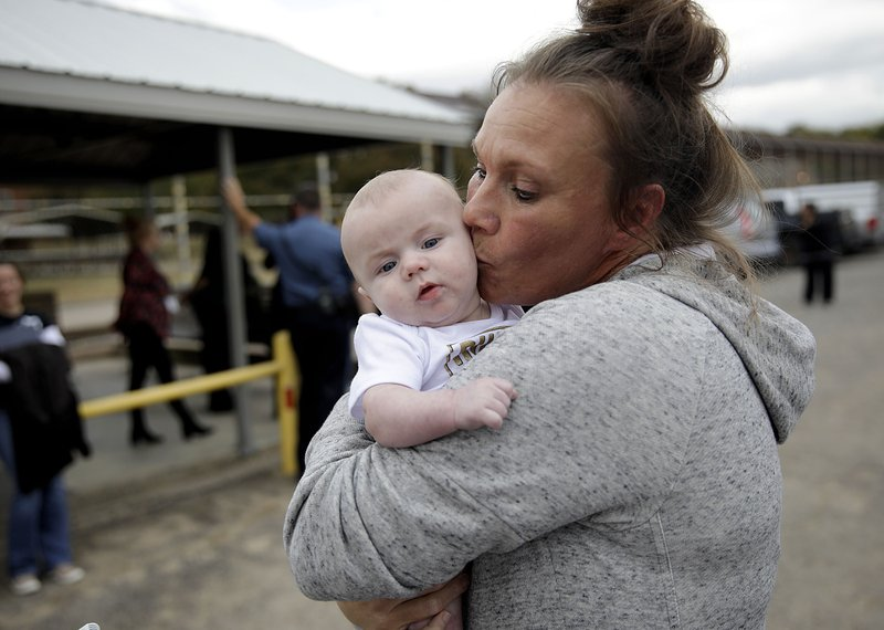 Lori Scott kisses her grandson Jasper Artigue, 3 mos., after being released from Dr. Eddie Warrior Correctional Center after having her sentence commuted by the state Monday, Nov. 4, 2019. It was the first time Scott held her grandson. (Mike Simons/Tulsa World via AP)