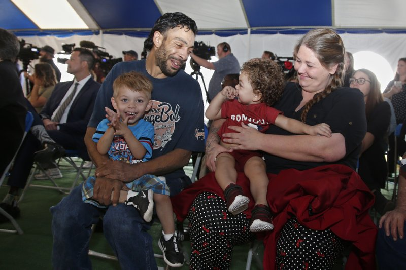 Recently released inmate Donnie Crow, right, holds her 17-month-old son Fayedon Davis as she celebrates with Christopher Davis Sr. and son 32-month old Christopher Davis II following her release Monday, Nov. 4, 2019 in Taft, Okla. More than 450 inmates walked out the doors of prisons across Oklahoma on Monday as part of what state officials say is the largest single-day mass commutation in U.S. history. (AP Photo/Sue Ogrocki)