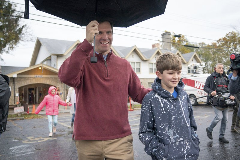 Kentucky Attorney General and Democratic Gubernatorial candidate Andy Beshear, and his son Will, 10, depart the Knights of Columbus polling location Tuesday, Nov. 5, 2019, in Louisville, Ky. Kentucky's voters are now deciding the political grudge match between Republican Gov. Matt Bevin and Beshear. (AP Photo/Bryan Woolston)