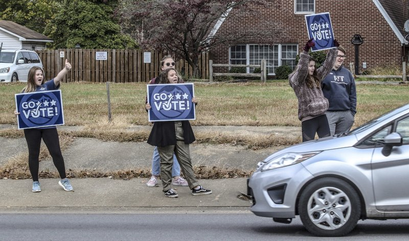 Lauren Payne, from left, Bella Karn, Victoria Garrard, Ella Bratcher and Connor Satterly encourage passing motorists to vote while standing on the sidewalk on W. Parrish Avenue, Tuesday, Nov. 5, 2019, in Owensboro, Ky. The five, all with the Wendell H. Ford Statesmanship Academy, and, other members of the organization, stood with signs at busy intersections in the city throughout election day. (Greg Eans/The Messenger-Inquirer via AP)