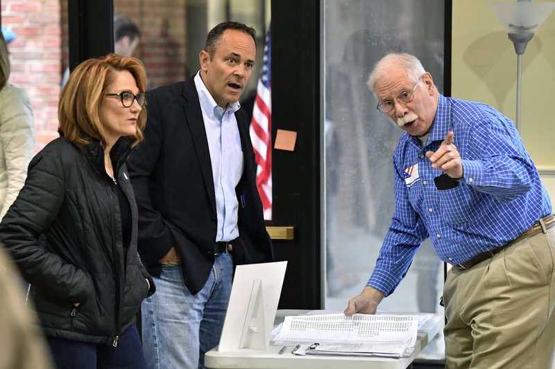 Kentucky Governor and Republican gubernatorial candidate Matt Bevin, center, and his wife Glenna Bevin are directed by a poll worker where they are to go to get their ballots for the state's general election in Louisville, Ky., Tuesday, Nov. 5, 2019. (AP Photo/Timothy D. Easley)