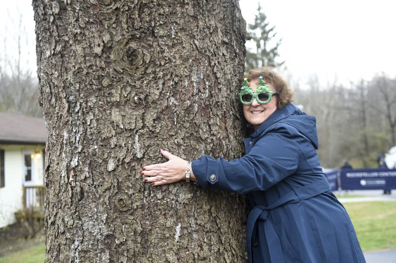 IMAGE DISTRIBUTED FOR TISHMAN SPEYER- Carol Schultz hugs the trunk of her 77-foot tall Norway Spruce that she donated to serve as this year's Rockefeller Center Christmas tree, Thursday, Nov. 7, 2019, in Florida, NY. The tree will be brought into New York City by flatbed truck and erected at Rockefeller Center on Saturday, Nov. 9. The 87th Rockefeller Center Christmas Tree Lighting ceremony will take place on Wednesday, Dec. 4. (Diane Bondareff/AP Images for Tishman Speyer)