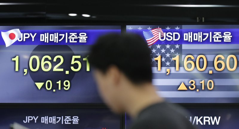 A currency trader stands by the screens showing the foreign exchange rates at the foreign exchange dealing room in Seoul, South Korea, Friday, Nov. 8, 2019. Asian stock markets were mixed Friday amid uncertainty about a possible U.S.-Chinese agreement to roll back tariffs in their trade war. (AP Photo/Lee Jin-man)
