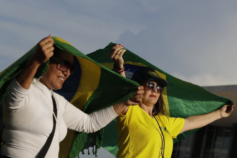Supporters of Brazil's President Jair Bolsonaro hold Brazilian national flags as they keep vigil outside the Supreme Court in Brasilia, Brazil, Thursday, Nov. 7, 2019. Brazil's highest court reached a narrow decision that could release almost 5,000 inmates who are still appealing their convictions, including jailed former President Luiz Inácio Lula da Silva. The country's Supreme Court decided on a 6-5 vote Thursday night that a person can be imprisoned only after all appeals to higher courts have been exhausted. (AP Photo/Eraldo Peres)