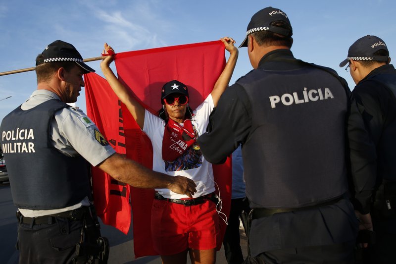 Police form a cordon between supporters of jailed former President Luiz Inacio Lula da Silva and President Jair Bolsonaro, as both groups keep vigil outside the Supreme Court in Brasilia, Brazil, Thursday, Nov. 7, 2019. Brazil's highest court reached a narrow decision that could release almost 5,000 inmates who are still appealing their convictions, including jailed former President Luiz Inácio Lula da Silva. The country's Supreme Court decided on a 6-5 vote Thursday night that a person can be imprisoned only after all appeals to higher courts have been exhausted. (AP Photo/Eraldo Peres)