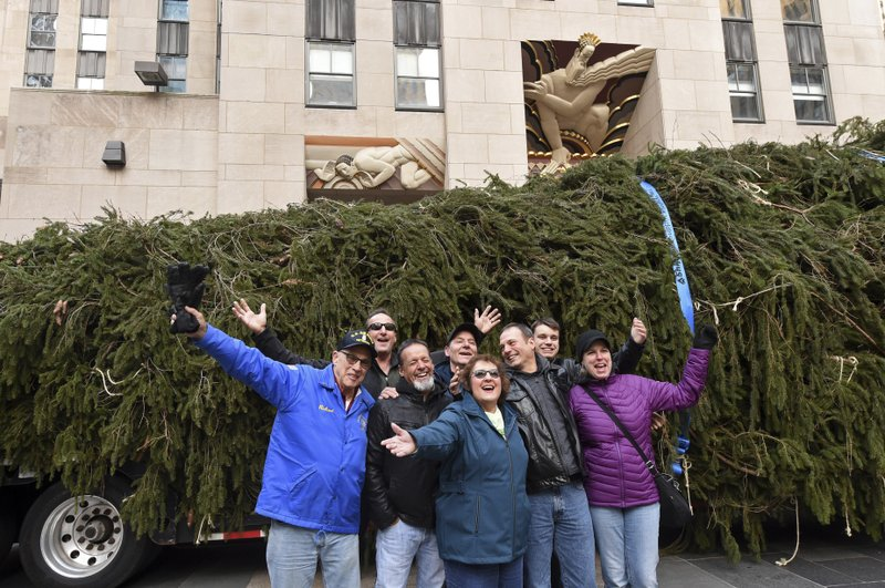 IMAGE DISTRIBUTED FOR TISHMAN SPEYER -  Carol Schultz, center, donor of this year's Rockefeller Center Christmas tree, poses with her family in front of her 77-foot tall Norway Spruce that she donated to serve as the 2019 Rockefeller Center Christmas tree, Saturday, Nov. 9, 2019, in New York. The 87th Rockefeller Center Christmas Tree Lighting ceremony will take place on Wednesday, Dec. 4. (Diane Bondareff/AP Images for Tishman Speyer)