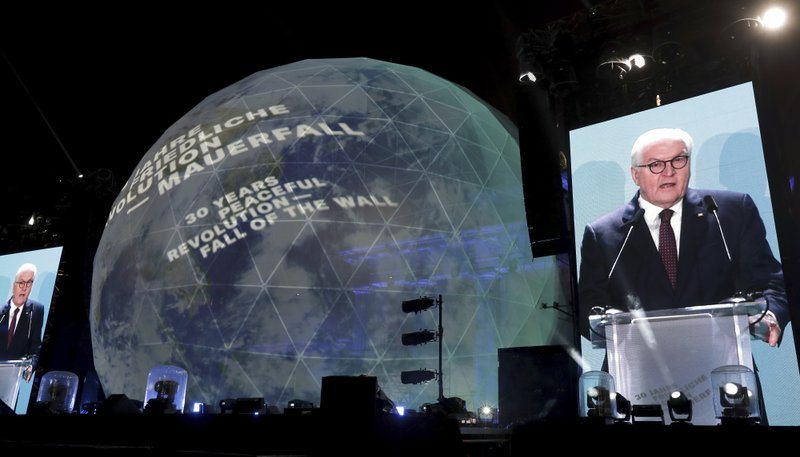 German President Frank-Walter Steinmeier is seen on giant video screens as he delivers a speech in front of the Brandenburg Gate as part of stage presentations to celebrate the 30th anniversary of the fall of the Berlin Wall in Berlin, Germany, Saturday, Nov. 9, 2019. (AP Photo/Michael Sohn)