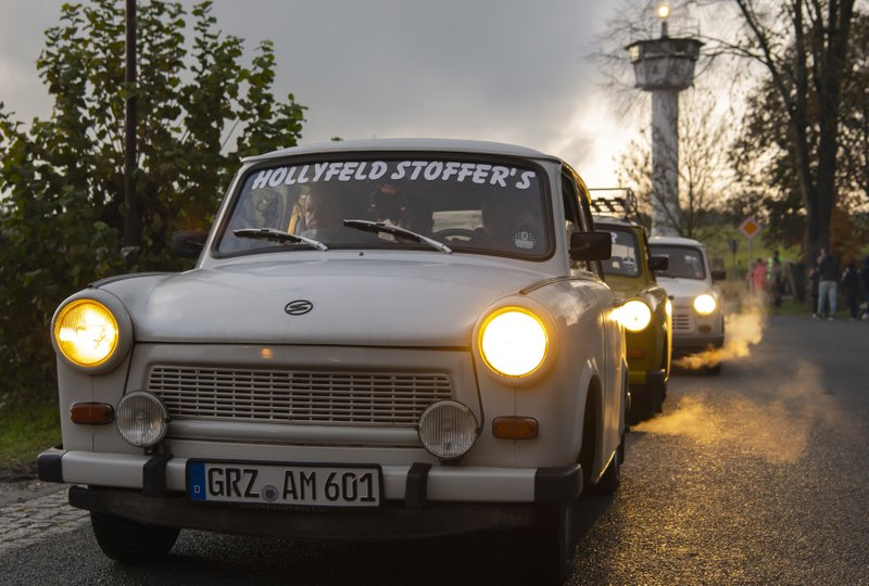 Legendary GDR Trabant (Trabi) cars,drive in front of a control tower of the former GDR border guard forces  during a symbolic wall opening, celebrating the 30th anniversary of the falling wall in the outdoor area of the German-German museum in Moedlareuth, Germany, Saturday, Nov. 9, 2019. Moedlareuth, named 'Little Berlin', was the symbol of a divided village along the borderline between East and West Germany. The border ran straight through the little village. (AP Photo/Jens Meyer)
