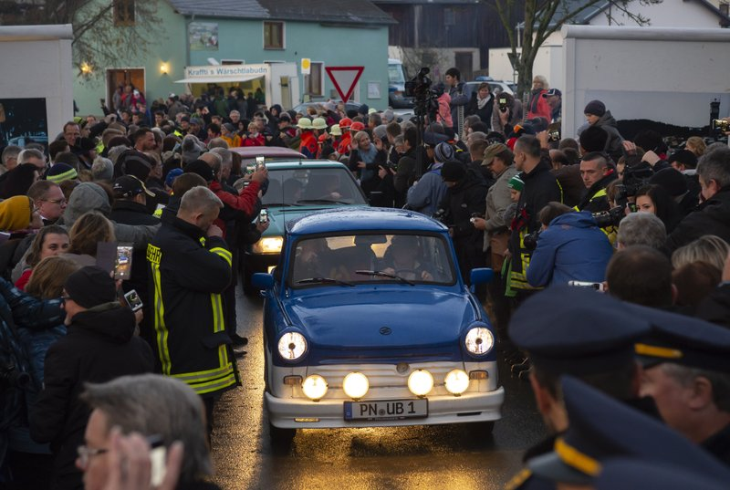 People welcome the legendary GDR Trabant (Trabi) cars, during a symbolic wall opening, celebrating the 30th anniversary of the falling wall in the outdoor area of the German-German museum in Moedlareuth, Germany, Saturday, Nov. 9, 2019. Moedlareuth, named 'Little Berlin', was the symbol of a divided village along the borderline between East and West Germany. The border ran straight through the little village. (AP Photo/Jens Meyer)