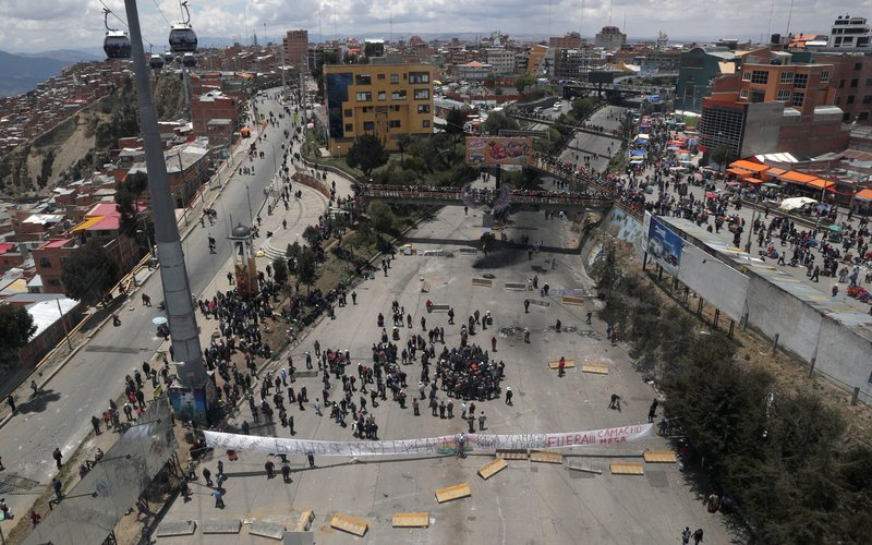 Supporters of Bolivian President Evo Morales block a road that connects La Paz and El Alto, to show their support of his apparent reelection in El Alto, Bolivia, Sunday, Nov. 10, 2019. President Morales is calling for new presidential elections and an overhaul of the electoral system Sunday after a preliminary report by the Organization of American States found irregularities in the Oct. 20 elections. (AP Photo/Juan Karita)