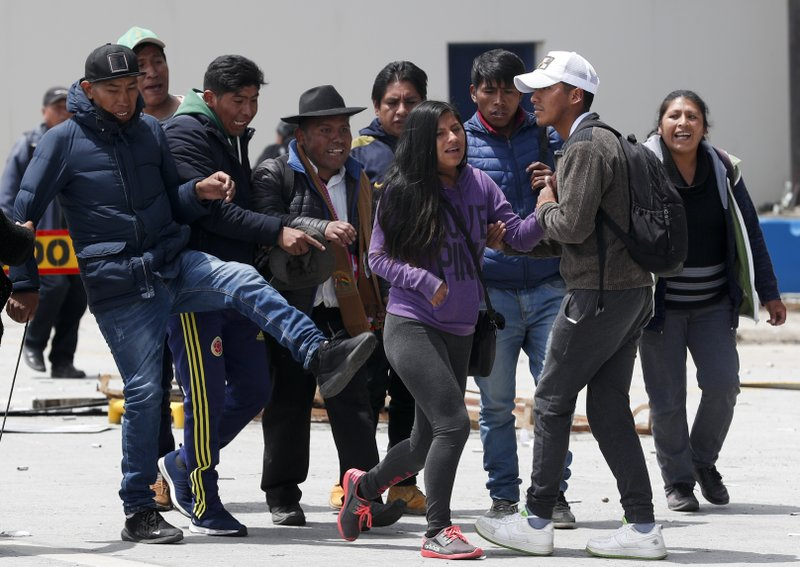 One person that is part of a group of followers of President Evo Morales kicks towards a couple in La Paz, Bolivia, Sunday, Nov. 10, 2019. President Evo Morales is calling for new presidential elections and an overhaul of the electoral system Sunday after a preliminary report by the Organization of American States found irregularities in the Oct. 20 elections. (AP Photo/Juan Karita)