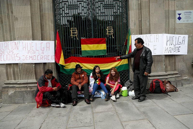 Anti-government protesters sit outside the presidential palace as a banner in the wall reads in Spanish