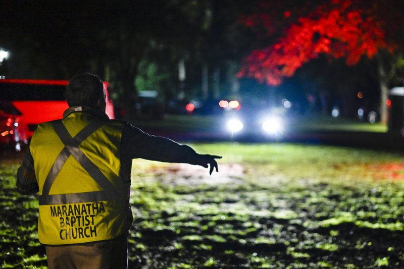 In this Sunday, Nov. 3, 2019, photo, Plains Mayor Boze Godwin directs cars into a pecan grove to park behind Maranatha Baptist Church before dawn, in Plains, Ga. Guests begin arriving the day before to attend the Sunday school class that former President Jimmy Carter teaches. (AP Photo/John Amis)