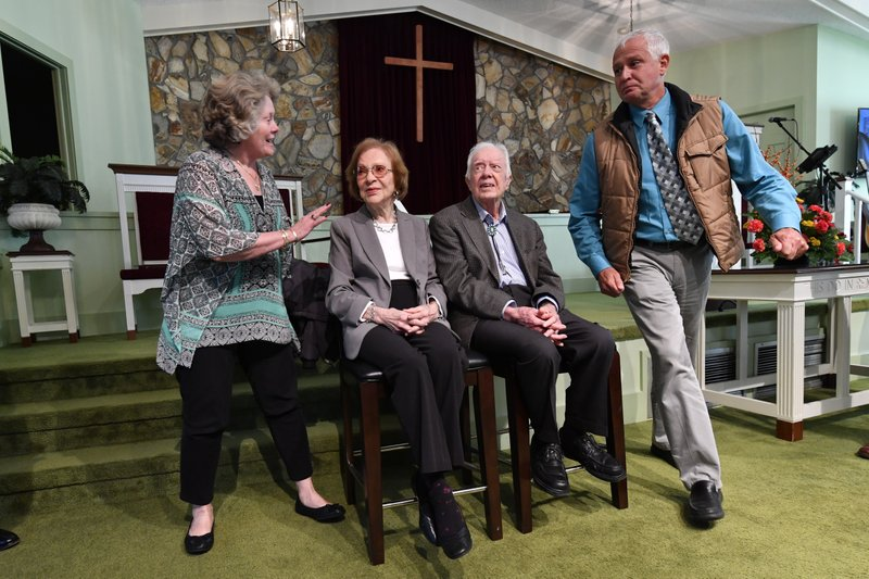 In this Sunday, Nov. 3, 2019, photo, former President Jimmy Carter, second from right, and former first lady Rosalynn Carter sit, as guests Romona Kluth, left, and husband Doug Kluth, from Nebraska, finish their turn of having their photo made with them, after Sunday school at Maranatha Baptist Church, in Plains, Ga. (AP Photo/John Amis)