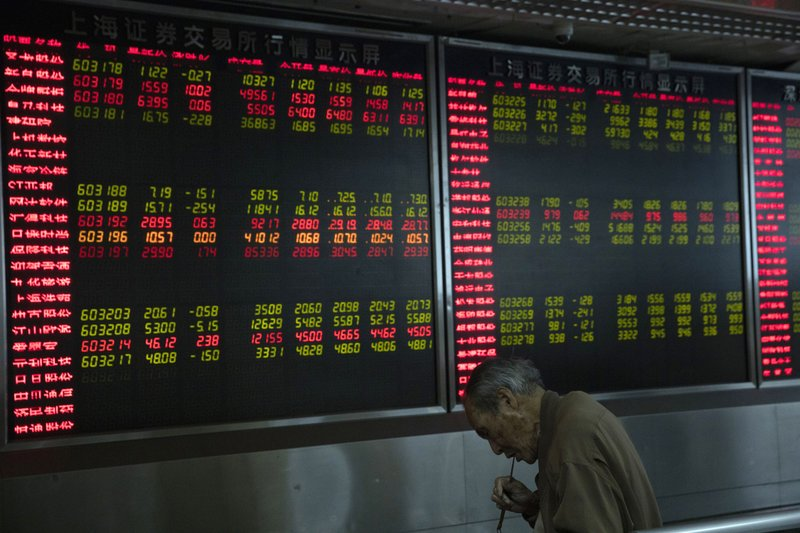 An investor eats a meal near a board displaying stock prices at a brokerage in Beijing Monday, Nov. 11, 2019. Shares declined Monday in Asia as investors watched for the latest developments in the China-U.S. trade war sage. (AP Photo/Ng Han Guan)