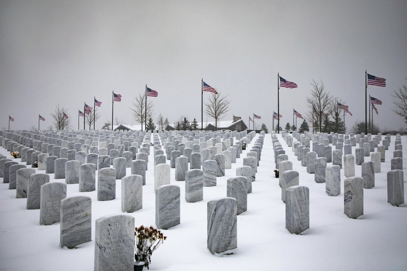 Snow covers graves where veterans are buried at The Great Lakes Cemetery  on Monday, Nov. 11, 2019, in Holly, Mich. (Rachel Ellis/Saginaw News via AP)