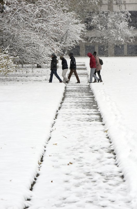 Students head to class Monday, Nov. 11, 2019, at Andrews University in Berrien Springs, Mich., after a fall storm dumped several inches of snow on southwest Michigan. (Don Campbell/The Herald-Palladium via AP)