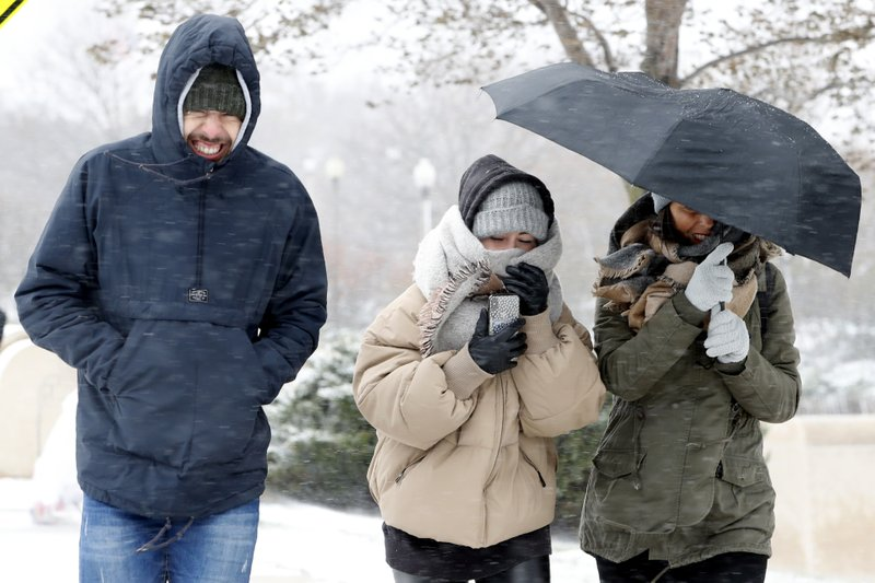 People walking the half mile from the Chicago Aquarium to the Adler Planetarium brace themselves as wind and snow blow Monday, Nov. 11, 2019, in Chicago. (AP Photo/Charles Rex Arbogast)