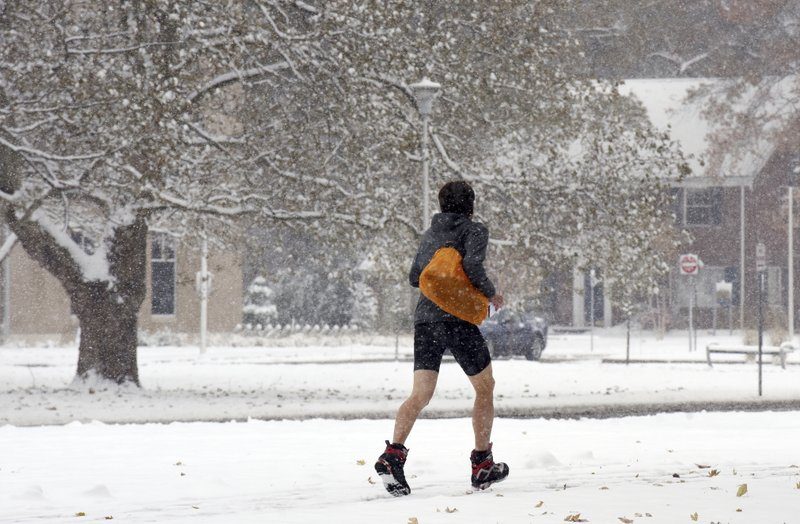 A student sprints through the snow on the campus of Andrews University in Berrien Springs, Mich., Monday, Nov. 11, 2019, after a fall snowstorm dumped several inches of snow on southwest Michigan. (Don Campbell/The Herald-Palladium via AP)