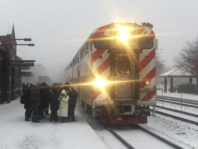 Commuters wait to board a Metra train in Naperville, Ill., Monday, Nov. 11, 2019, in Chicago. (Rich Hein/Chicago Sun-Times via AP)