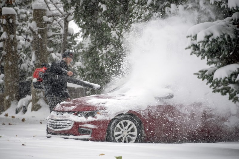 Jeremy Kohsman uses a leaf blower to remove the snow from his car in front of his home in Farmington Hills, Mich., Monday, Nov. 11, 2019. (David Guralnick/Detroit News via AP)
