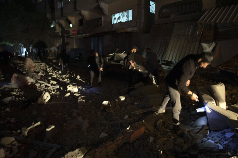Palestinians check the damage of a house targeted by Israeli missile strikes in Gaza City, Tuesday, Nov. 12, 2019. The Israeli military says it has struck a Gaza City house, targeting a commander from the Islamic Jihad group in a resumption of pinpointed killing. The Iranian-backed Palestinian group confirmed Tuesday that Bahaa Abu el-Atta, it's north Gaza Strip commander, was killed. (AP Photo/Khalil Hamra)