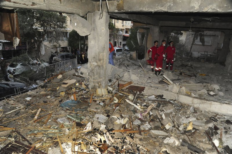 In this photo released by the Syrian official news agency SANA, Syrian officials check the damage of a building targeted by Israeli missile strikes in the early morning in the Mezzeh area in the capital Damascus, Syria, Tuesday, Nov. 12, 2019. Syria's state-run news agency says Israel has struck a residential building in Damascus housing a commander of the Palestinian Islamic Jihad group with two missiles, killing two people. (SANA via AP)