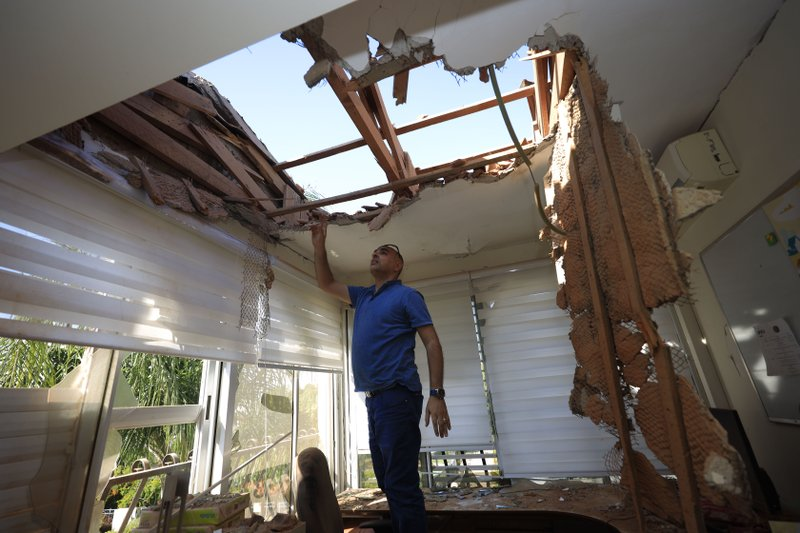 A man looks at the damage to a house in Sderot, Israel, after it was hit by a rocket fired from Gaza Strip, Tuesday, Nov. 12m 2019. Israel has killed a senior Islamic Jihad commander in Gaza in a rare targeted killing that threatened to unleash a fierce round of cross-border violence with Palestinian militants. (AP Photo/Tsafrir Abayov)