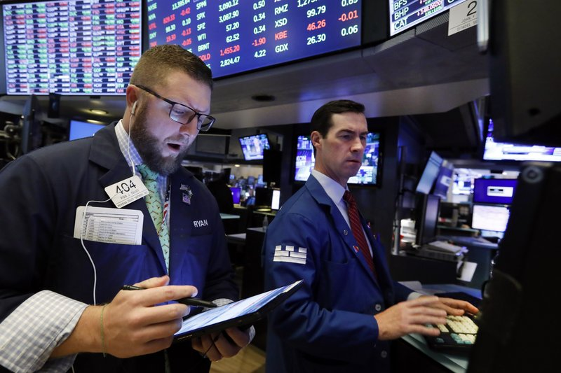 Trader Ryan Falvey, left and specialist John McNierney work on the floor of the New York Stock Exchange, Tuesday, Nov. 12, 2019. Stocks are opening slightly higher on Wall Street, led by gains in technology and health care companies. (AP Photo/Richard Drew)